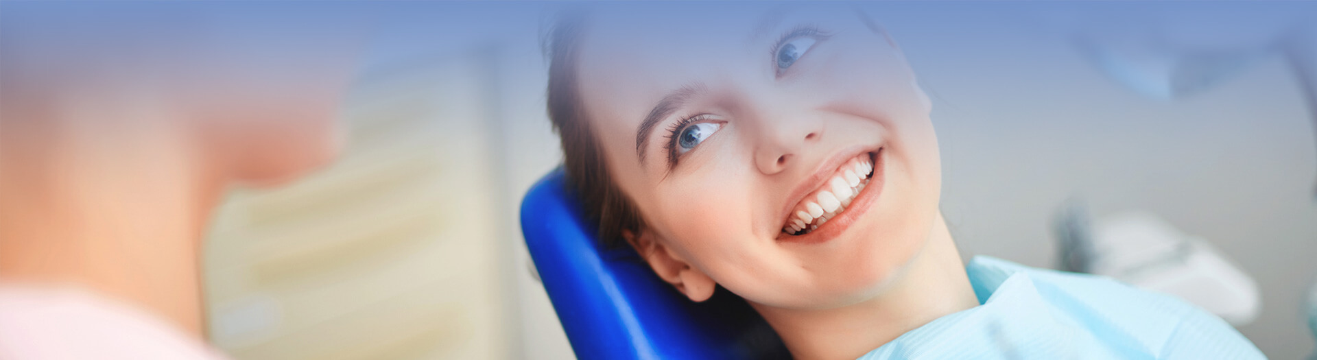 Young woman sitting in dentist office and looking at her doctor with smile
